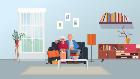 Elderly couple sitting on couch in living room with plants, books and a bookshelf.