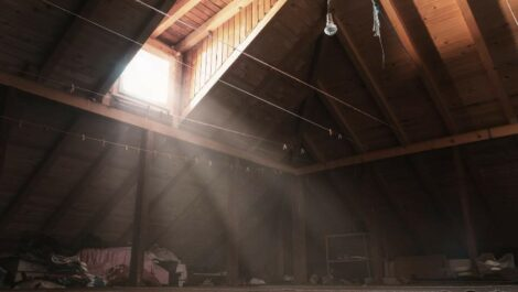 Attic with a window and sunbeam of light shining into the space.