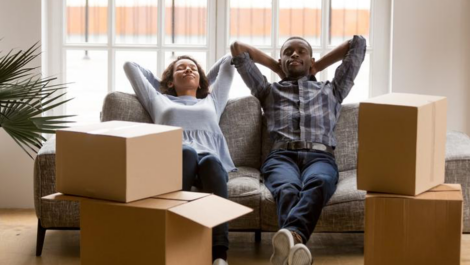 Couple relaxing on couch next to storage boxes.