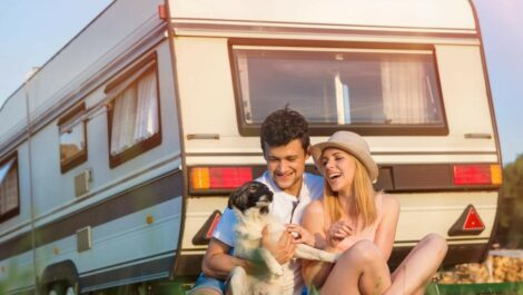 Couple and a dog relaxing and smiling in front of RV.