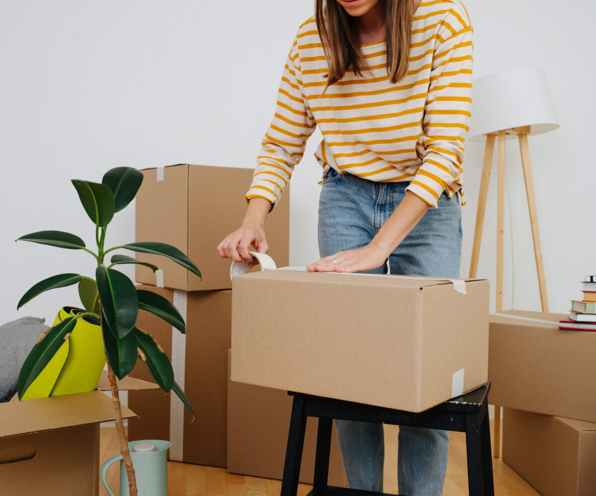 Person taping a moving box.